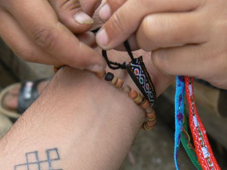 """Tying friendship bracelet"" by Satbir Singh - Flickr. Licensed under Creative Commons"